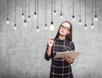 Mädchen mit einem Buch, Glühlampen, konkret Stockbild