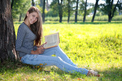 Mädchen mit einem Buch im Park Stockbilder