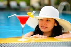 Mädchen mit einem Cocktail am Rand des Swimmingpools lizenzfreie stockbilder
