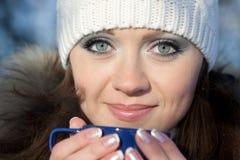 Mädchen mit einem Cup eines heißen Getränks Stockbild