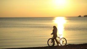 Mädchen mit einem Fahrrad geht entlang den Strand bei Sonnenuntergang Romantisches Mädchen stock video footage