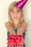 Mädchen mit einem Geburtstagsgeschenk und -kappe Lizenzfreie Stockfotografie