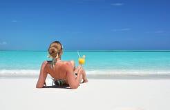 Mädchen mit einem Glas der Orange auf dem Strand Stockfotos
