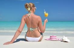 Mädchen mit einem Glas der Orange auf dem Strand Lizenzfreies Stockbild