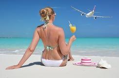 Mädchen mit einem Glas Orangensaft auf dem Strand Stockbilder