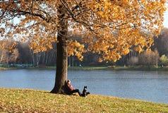Mädchen mit einem Hund, der auf dem Ufer des Teichs sitzt Lizenzfreie Stockfotos
