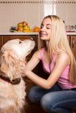 Mädchen mit einem Hund in der Küche Stockbilder
