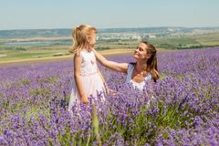 Mädchen mit einem Kind auf einem Gebiet des Lavendels Stockfotografie