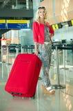 Mädchen mit einem Koffer am Flughafen Lizenzfreie Stockbilder
