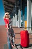 Mädchen mit einem Koffer nahe dem Flughafen Stockfotografie