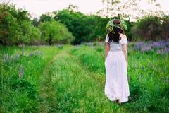 Mädchen mit einem Kranz von Wildflowers auf ihren Hauptwegen lizenzfreie stockfotos