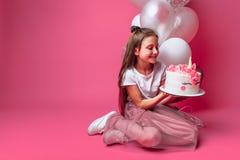 Mädchen mit einem Kuchen für einen Geburtstag, im Studio auf einem rosa Hintergrund, festliche Stimmung lizenzfreie stockfotografie