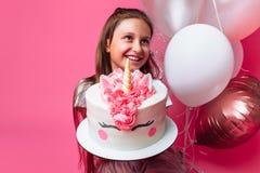 Mädchen mit einem Kuchen für einen Geburtstag, im Studio auf einem rosa Hintergrund, festliche Stimmung lizenzfreie stockfotos