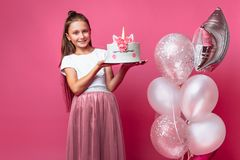 Mädchen mit einem Kuchen für einen Geburtstag, im Studio auf einem rosa Hintergrund, festliche Stimmung lizenzfreies stockfoto