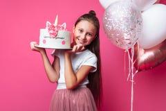 Mädchen mit einem Kuchen für einen Geburtstag, im Studio auf einem rosa Hintergrund, festliche Stimmung, Abschluss- oben, Designe lizenzfreie stockbilder