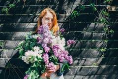 Mädchen mit einem lila Blumenstrauß der Flieder im Garten Mädchen, welches die Flieder im Garten zerreißt stockbild