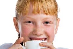Mädchen mit einem Milchbecher Stockbild