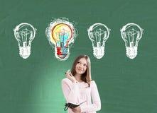 Mädchen mit einem Notizbuch und vier Glühlampen, grün Stockfoto