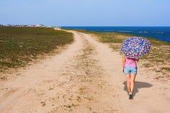 Mädchen mit einem Regenschirm geht auf Küste Stockfotografie