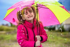 Mädchen mit einem Regenschirm genießen Niederschlag lizenzfreie stockbilder