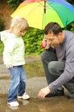 Mädchen mit einem Regenschirm im Regen mit seinem Vater Stockfoto