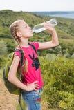 Mädchen mit einem Rucksack, der auf dem Hintergrund des Sees und des Trinkwassers steht Lizenzfreie Stockbilder