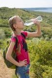 Mädchen mit einem Rucksack, der auf dem Hintergrund des Sees und des Trinkwassers steht Stockfotografie