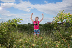 Mädchen mit einem Rucksack, der auf dem Hintergrund des Sees und des Trinkwassers steht Stockbilder