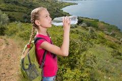 Mädchen mit einem Rucksack, der auf dem Hintergrund des Sees und des Trinkwassers steht Stockfotos