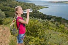 Mädchen mit einem Rucksack, der auf dem Hintergrund des Sees und des Trinkwassers steht Lizenzfreies Stockbild