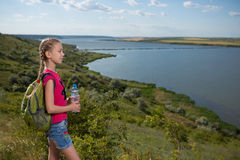 Mädchen mit einem Rucksack, der auf dem Hintergrund des Sees und des Trinkwassers steht Lizenzfreies Stockfoto