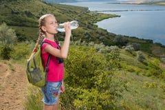 Mädchen mit einem Rucksack, der auf dem Hintergrund des Sees und des Trinkwassers steht Stockbild