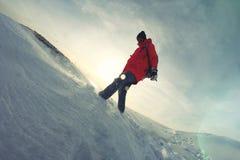 Mädchen mit einem Rucksack im Winter kleidet das Gehen auf den Schnee Lizenzfreie Stockbilder
