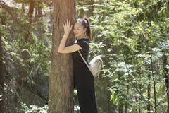 Mädchen mit einem Rucksack umarmt einen Baum mit ihren Augen, die in t geschlossen werden lizenzfreie stockfotos