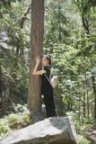 Mädchen mit einem Rucksack umarmt einen Baum mit ihren Augen, die in t geschlossen werden stockbild