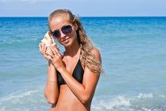 Mädchen mit einem Seashell auf dem Meer. Stockfoto