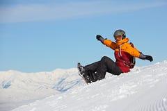 Mädchen mit einem Snowboard, der auf der Steigung sitzt und freut sich Stockbilder