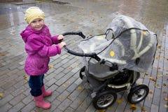 Mädchen mit einem Spaziergänger. Lizenzfreies Stockfoto