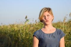 Mädchen mit einem Stroh in ihrem Mund gegen einen Hintergrund von Reeddickichten Lizenzfreie Stockbilder