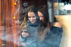 Mädchen mit einem Telefon, beste Freunde in einem Café Schießen hinter stockfotos