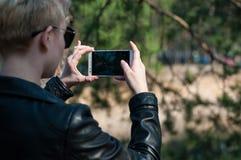 Mädchen mit einem Telefon in ihren Händen Lizenzfreies Stockbild