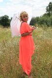 Mädchen mit einem weißen Regenschirm, ein langes Kleid, ein Feld von Blumen, ein rosa Kleid schönes blondes Mädchen auf einem Geb Stockfoto