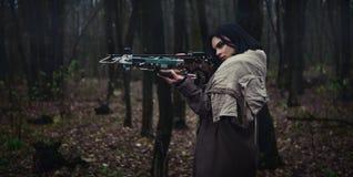 Mädchen mit einer Armbrust im Waldherbstwald Stockbild