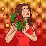 Mädchen mit einer Geschenkpop-art Schöner Brunette im roten Kleid hält einen Kasten mit Band Stockfotografie