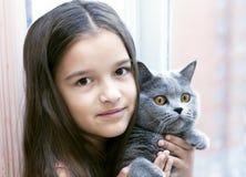 Mädchen mit einer Katze, die morgens am Fenster lächelt Stockfotografie
