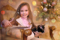 Mädchen mit einer Katze in einem Stuhl Stockbild