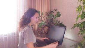 Mädchen mit einer Kreditkarte im Laptop stock video