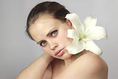 Mädchen mit einer Lilie auf einer Schulter Stockfoto