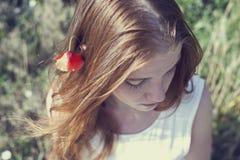 Mädchen mit einer Mohnblume in ihrem Haar Stockbilder