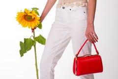 Mädchen mit einer roten Handtasche und einer Sonnenblume Stockbild